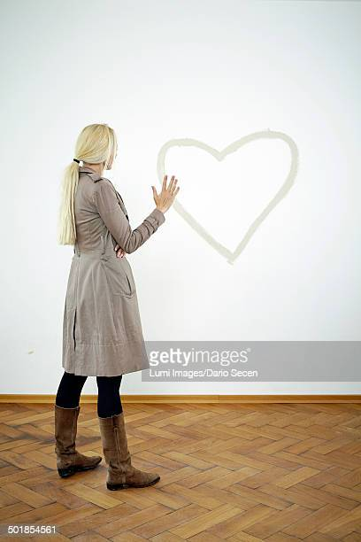 Young woman looking at heart shape on wall, Munich, Bavaria, Germany