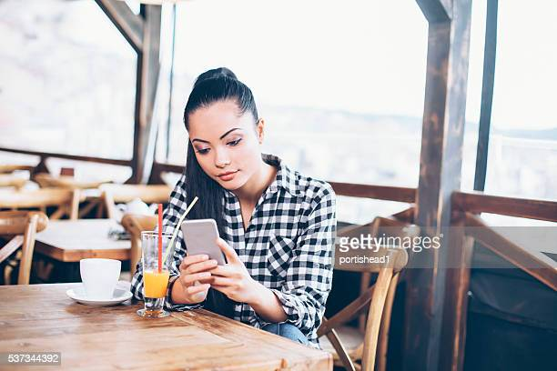 Young woman looking at her phone in the cafe shop