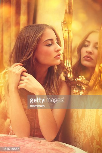 young woman looking at herself in a mirror : Stock Photo