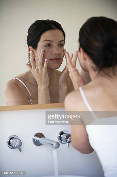 Young woman looking at herself in bathroom mirror