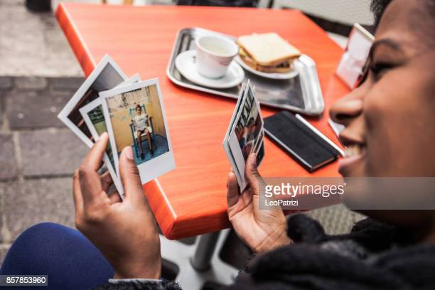 Young woman looking at instant camera photo frames