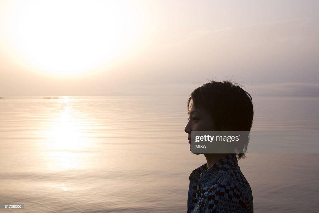 Young woman looking at lake : Stock Photo