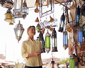 Young woman looking at lamp shades in shop