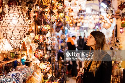 Young woman looking at lights on market stall, Istanbul, Turkey