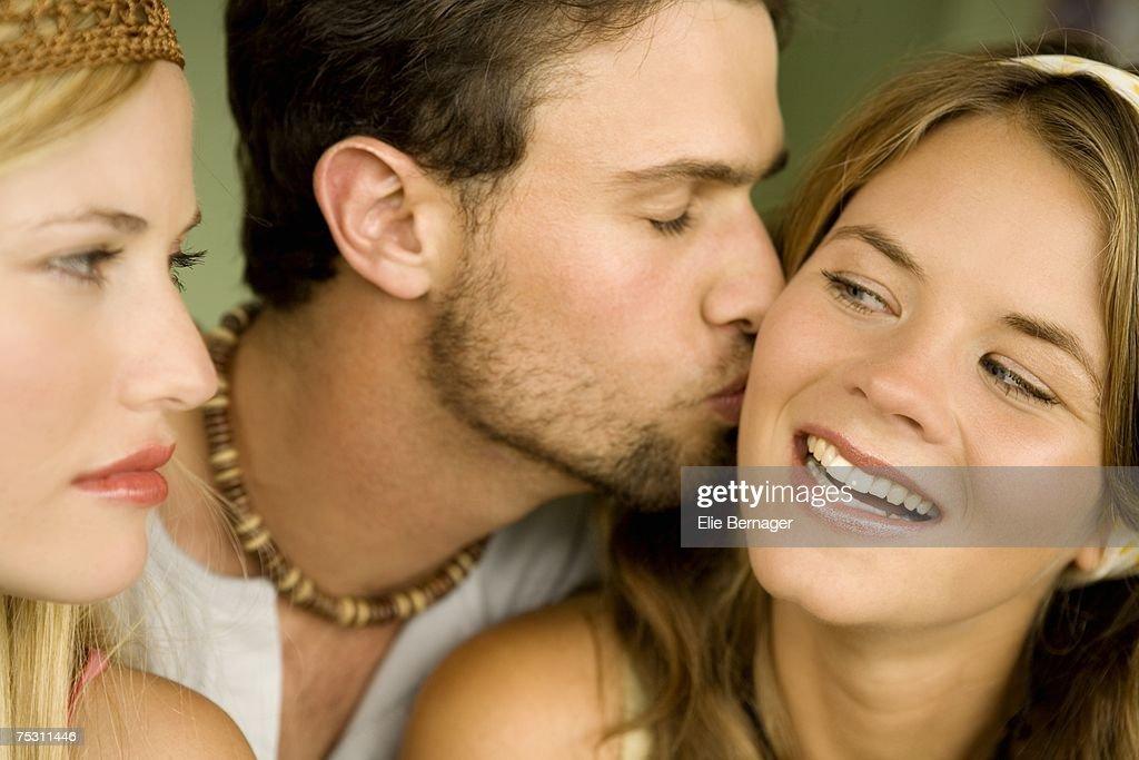 Young woman looking at man kissing smiling woman