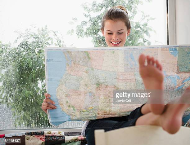 Young woman looking at map on rainy day