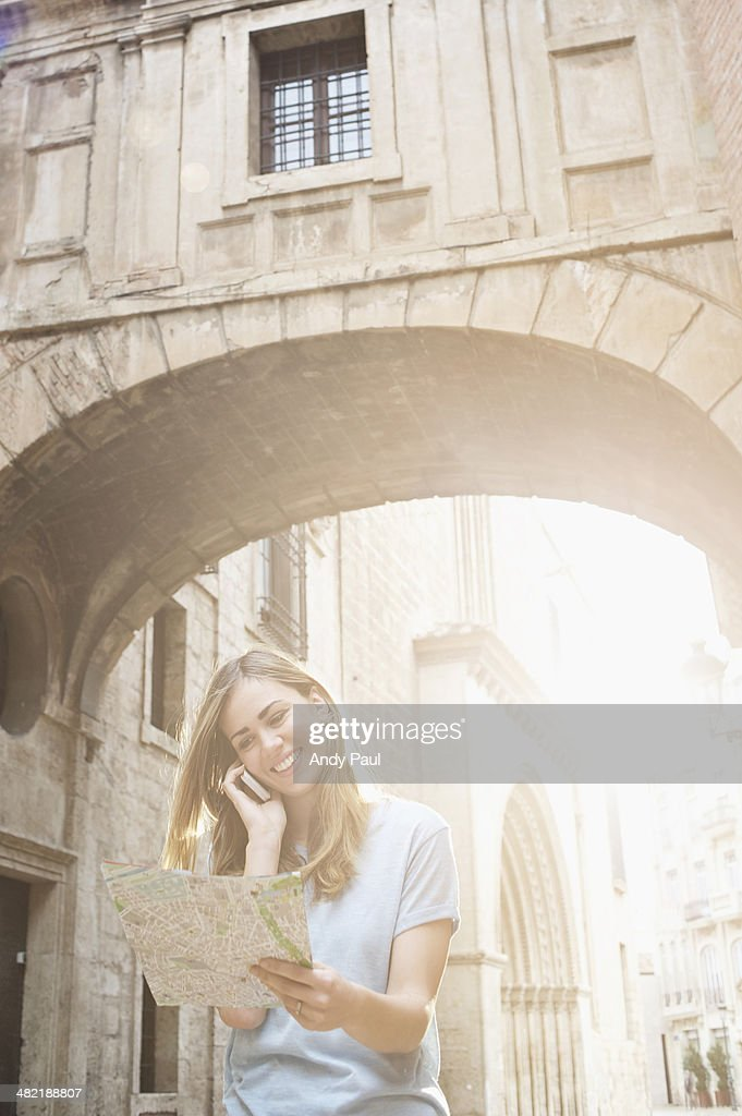 Young woman looking at map outside Valencia Cathedral, Valencia, Spain