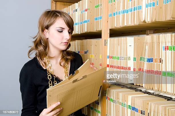 Young woman looking at medical records folders