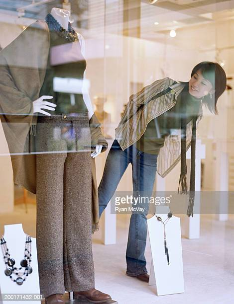 Young woman looking at outfit in boutique window, view through window