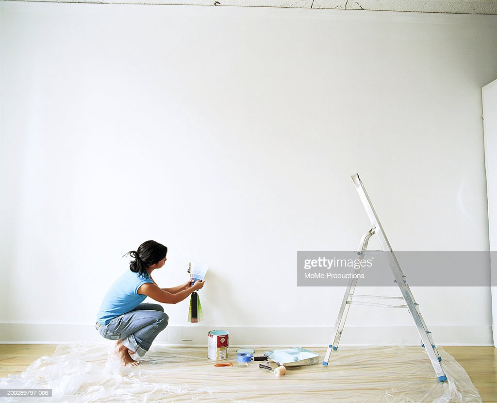 Young woman looking at paint samples, side view : Stock Photo