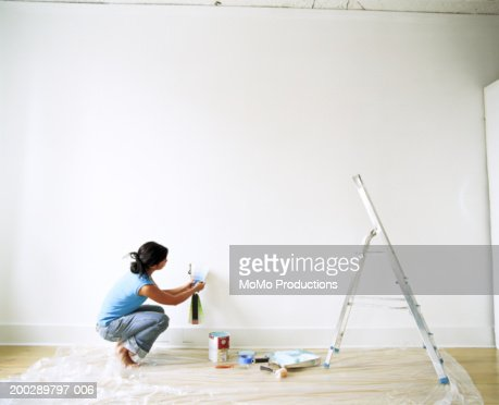 Young woman looking at paint samples, side view : Stockfoto