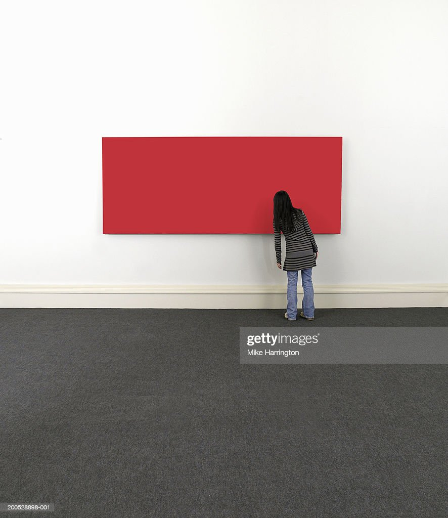 Young woman looking at painting on wall, rear view : Stock Photo