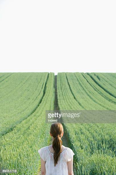 Young woman looking at path in wheat field