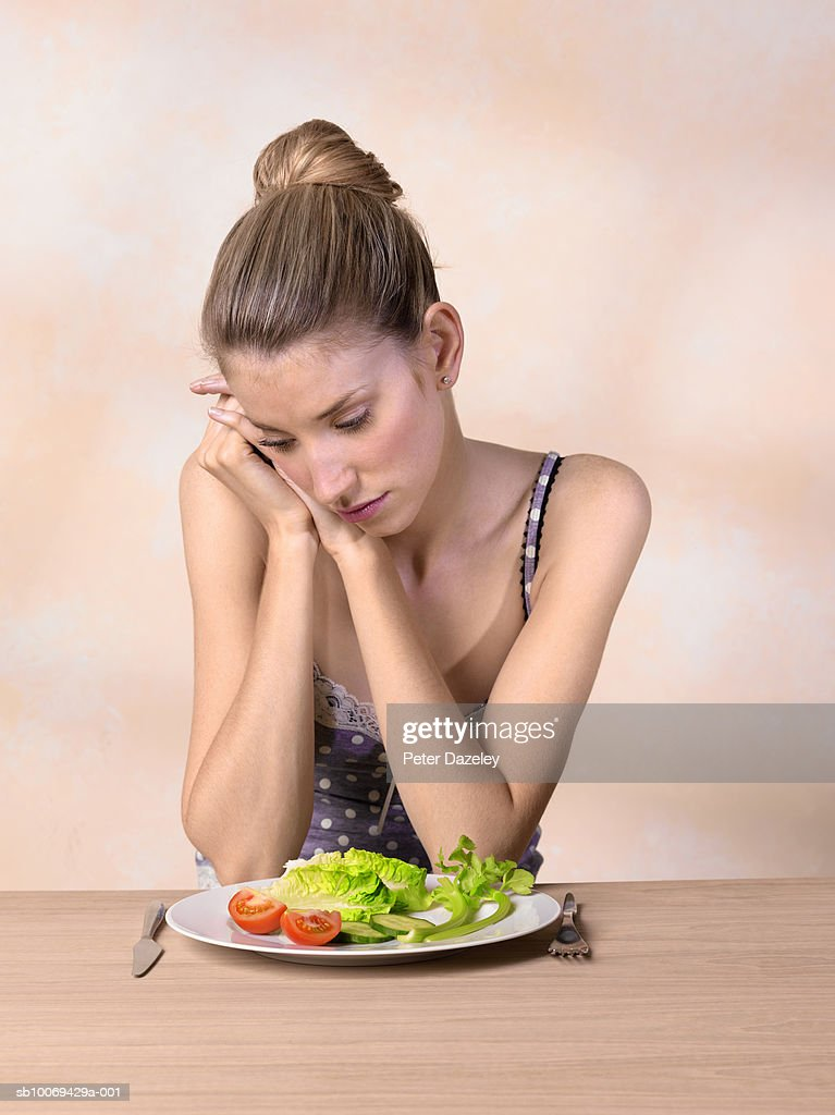 Young woman looking at plate of salad