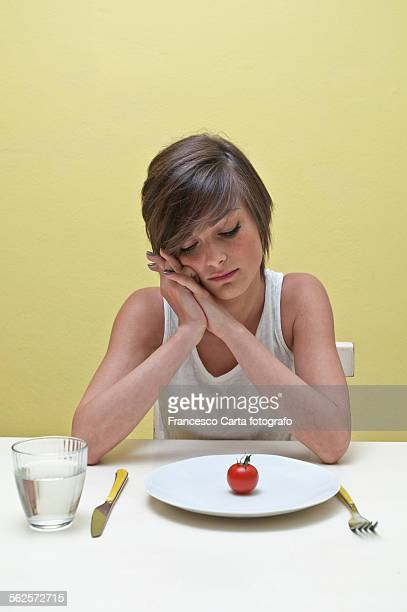 Young woman looking at plate of tomato