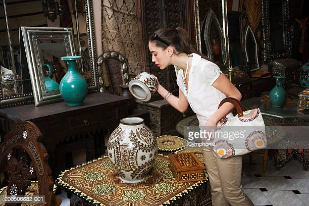Young woman looking at pot in antique market shop
