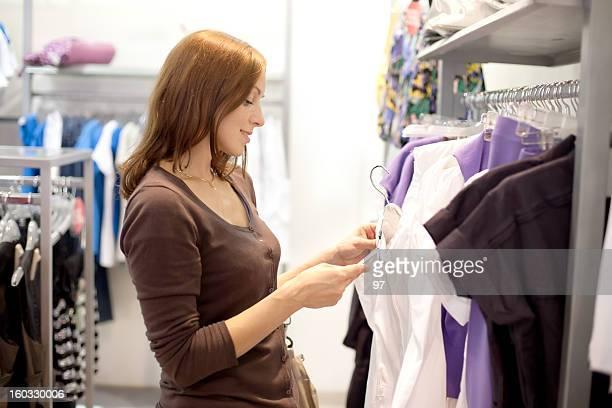 Hermosa mujer de compras en la tienda de ropa.
