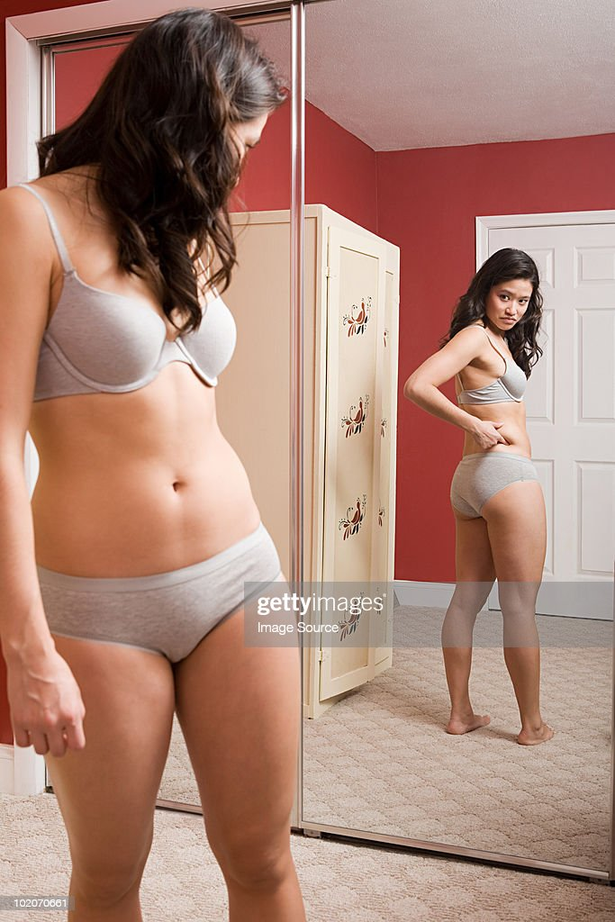 Young woman looking at reflection in mirror : Stock Photo