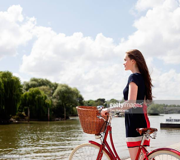 Young woman looking at river view with bike