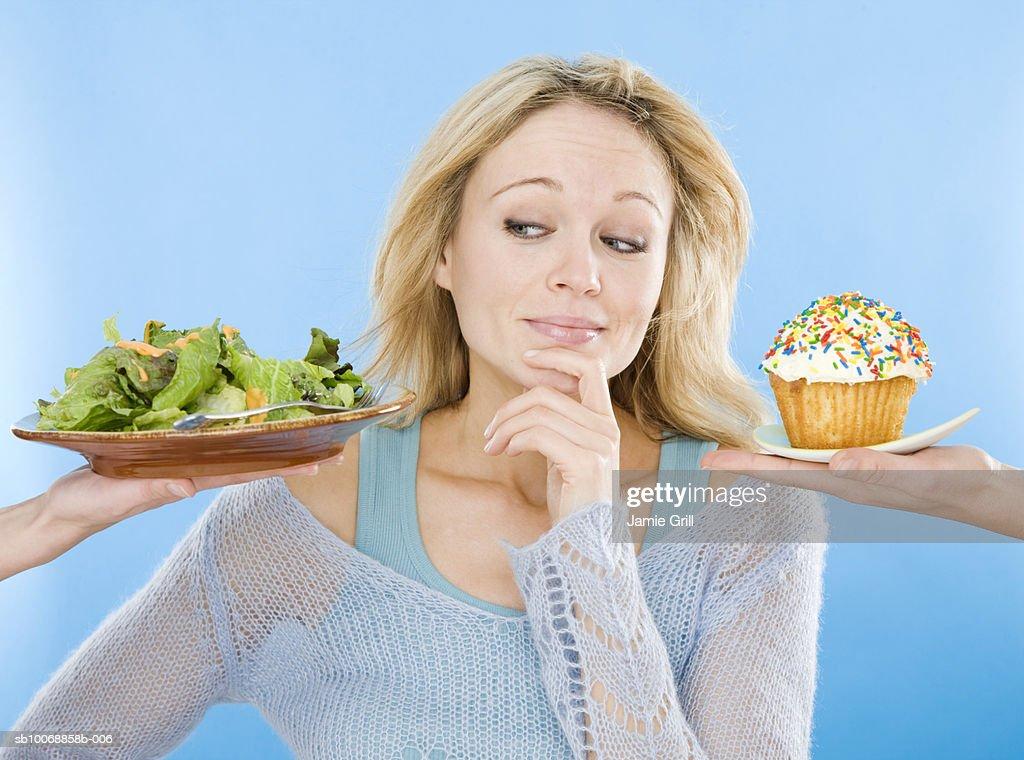 Young woman looking at salad and cupcake, hand on chin, close-up : Stock Photo