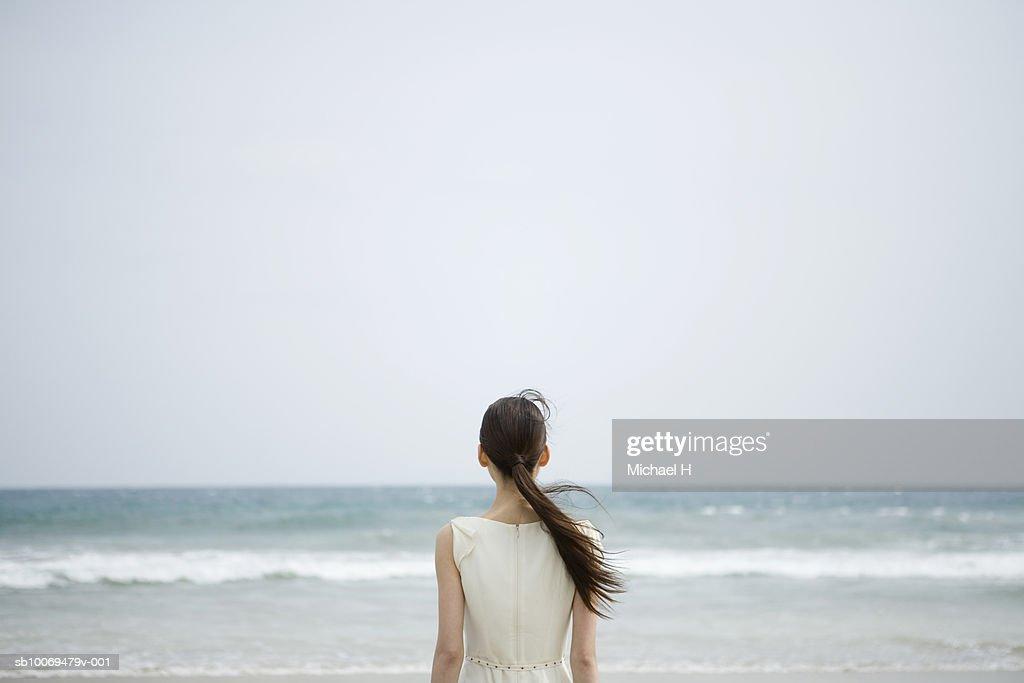 Young woman looking at sea, rear view : Stock Photo