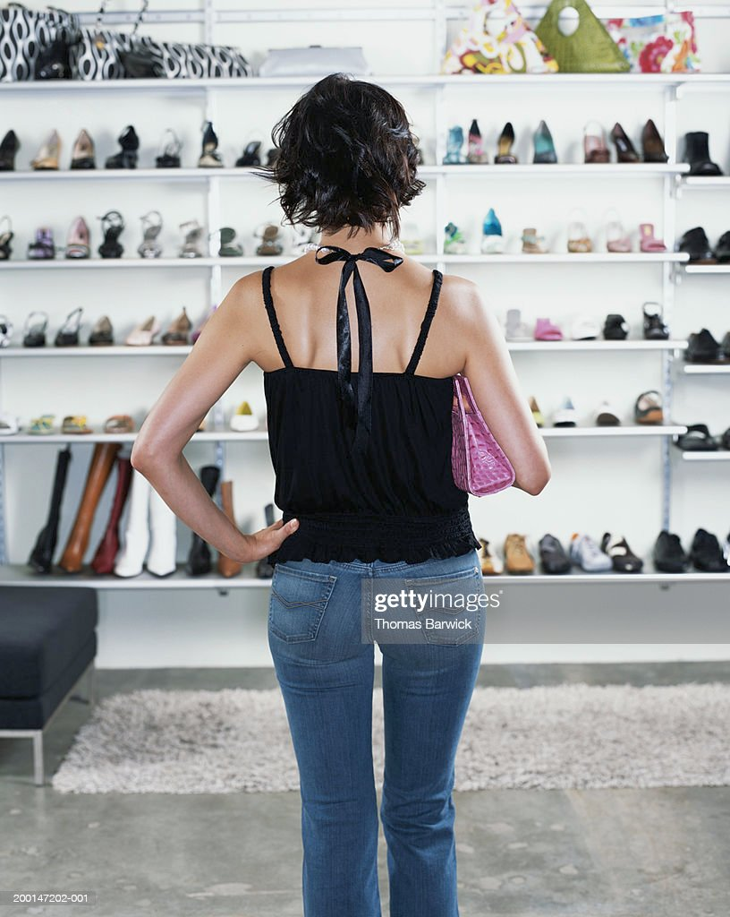 Young woman looking at shoes in shoe store, hand on hip, rear view