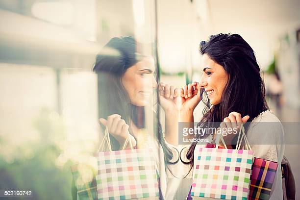 Young woman looking at shop window