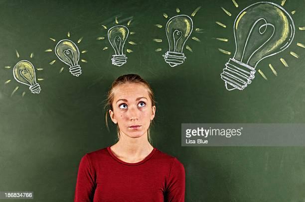 Junge Frau auf der Suche in skizzierte Glühbirnen