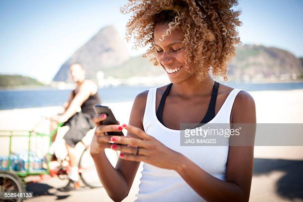 Young woman looking at smartphone, smiling