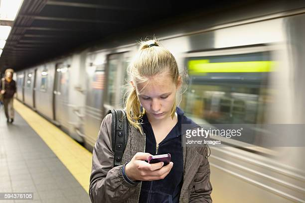 Young woman looking at smartphone, train on background