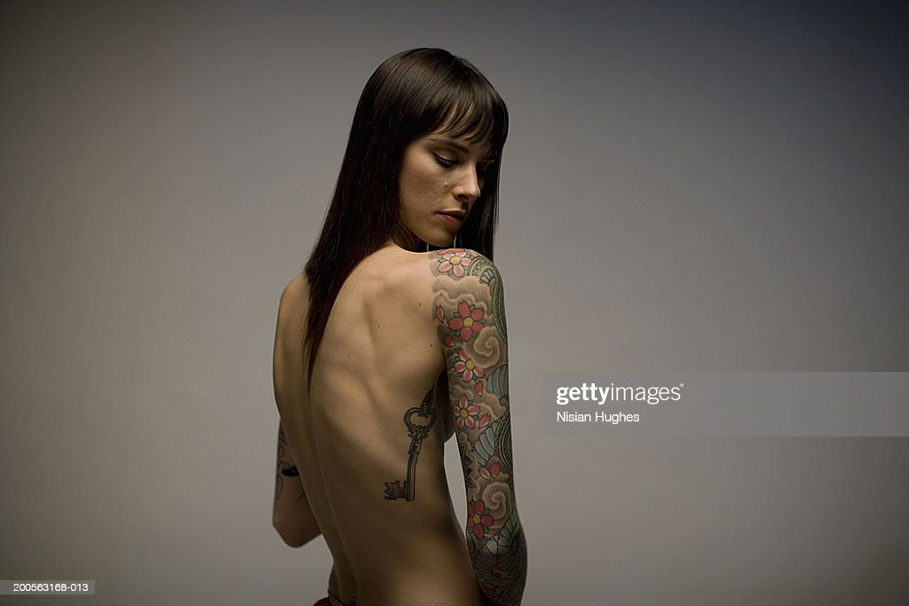Young woman looking at tattoo on arm : Stock Photo