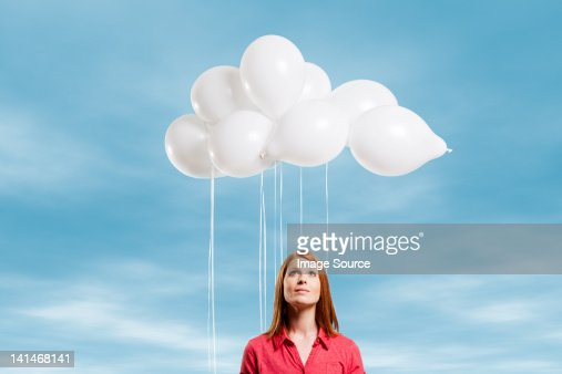 Young woman looking at thought bubble made of balloons : Stock Photo