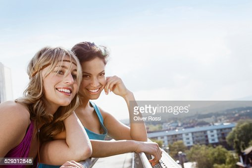 Young woman looking at town from rooftop : Stockfoto