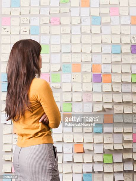 Young woman looking at wall covered with adhesive notes