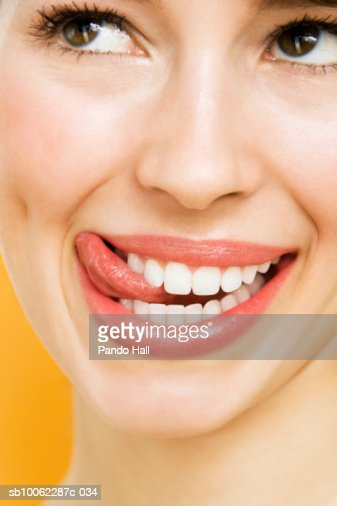 Young woman looking away and smiling, licking lips, close-up : Bildbanksbilder