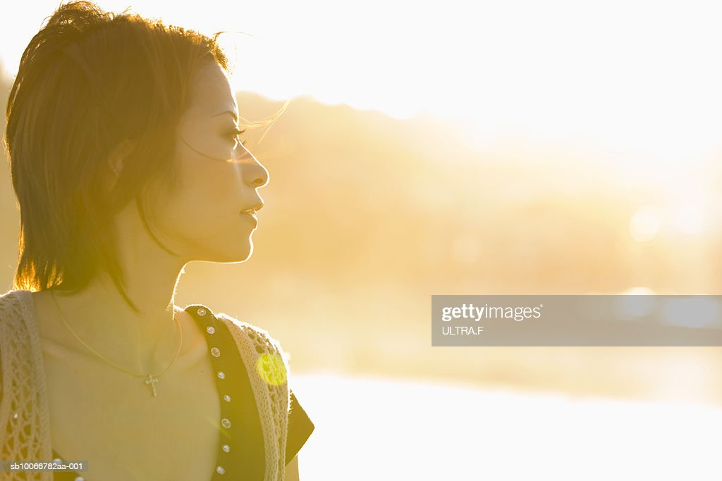 Young woman looking away at sunset : Stock Photo