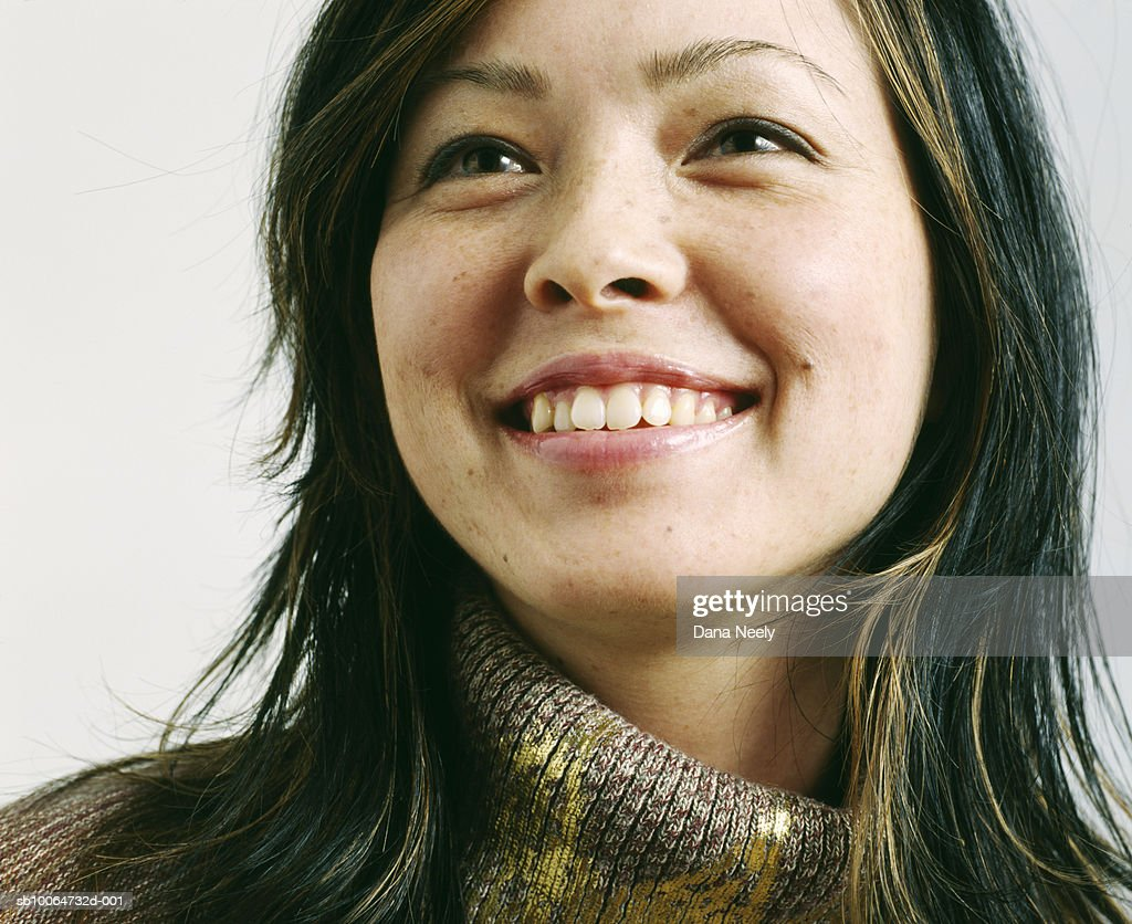 Young woman looking away, smiling, close-up : Stock Photo