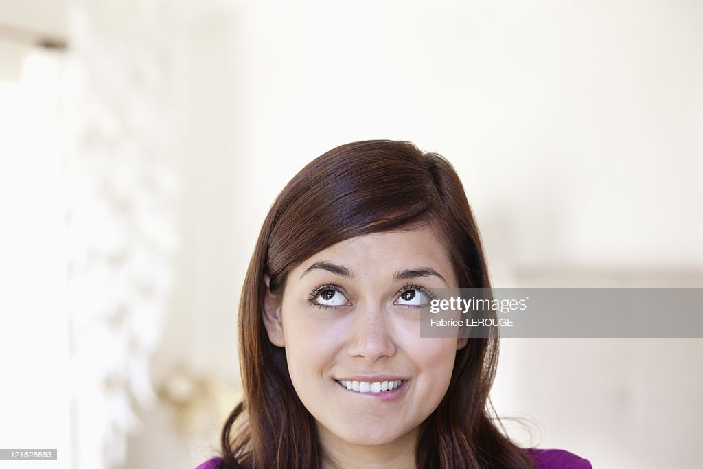 Young woman looking away while biting lips