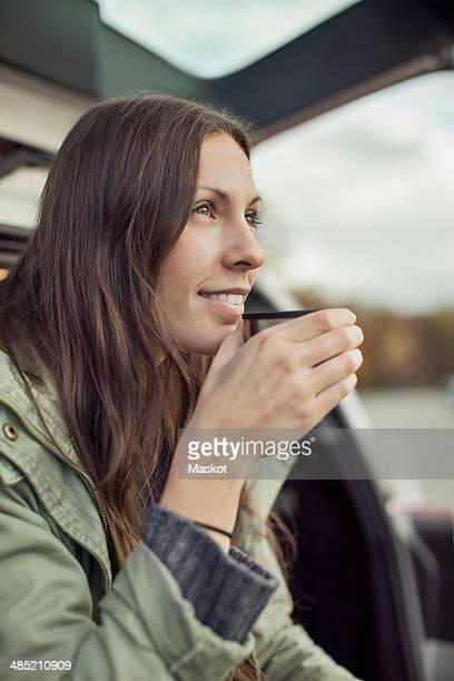 Young woman looking away while drinking coffee at car's trunk