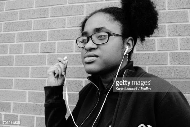 Young Woman Looking Away While Listening Music Through Headphones Against Brick Wall
