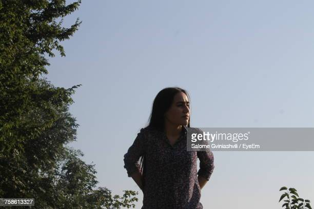 Young Woman Looking Away While Standing Against Clear Sky