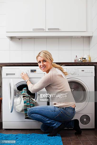 Young woman looking away while turning washing machine dial in bathroom