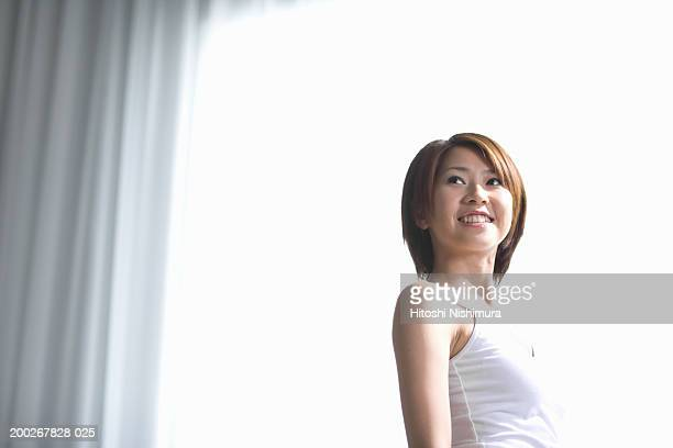 Young woman looking back over shoulder, smiling, low angle view