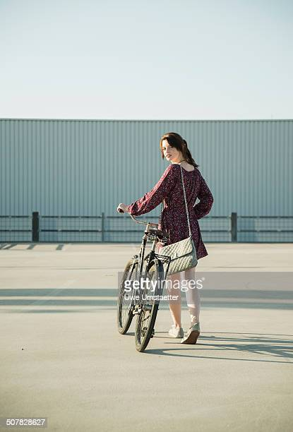 Young woman looking back whilst pushing bicycle in empty parking lot