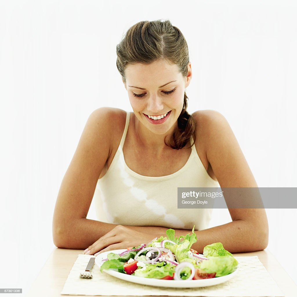 Young woman looking down at a plate of salad : Stock Photo