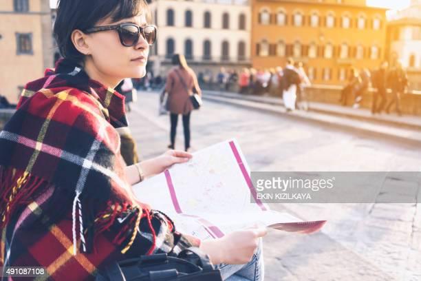 Joven mujer buscando dirección en la ciudad