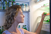 Young woman looking for food in fridge