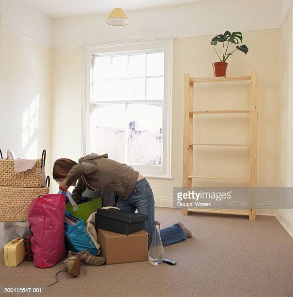 Young woman looking in bags on floor