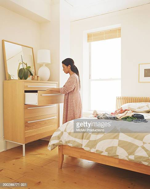 Young woman looking in dresser drawer in bedroom, side view