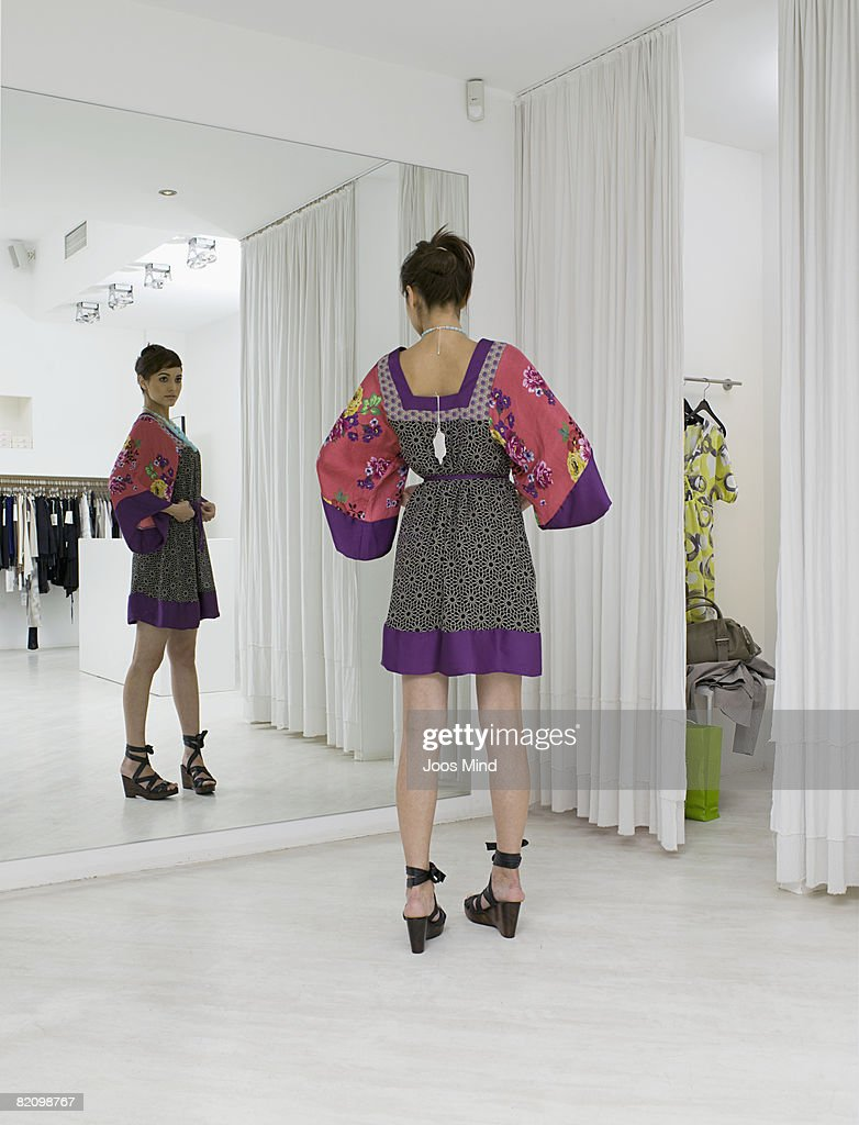 young woman looking in mirror beside fitting room